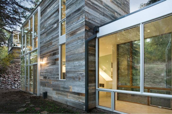 Kuća kraj reke obložena recikliranim drvetom
