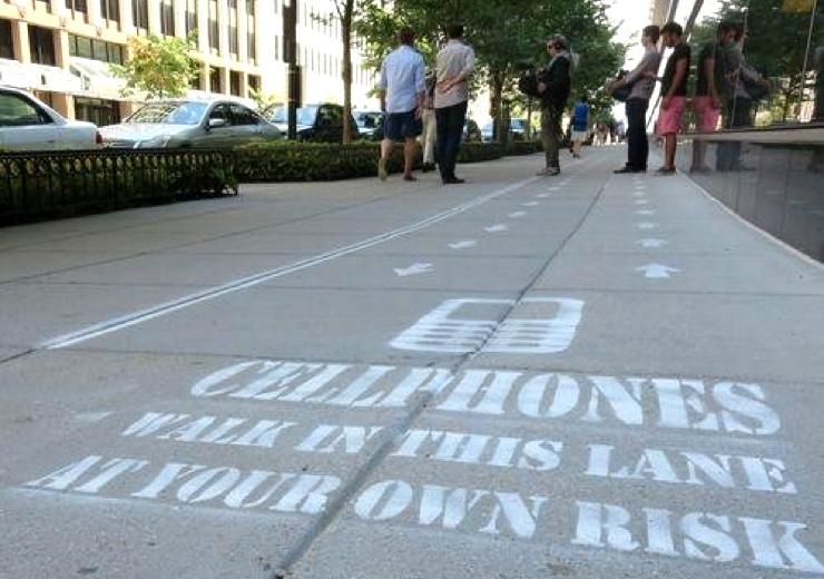 Odvojen trotoar za pešake s mobilnim telefonom