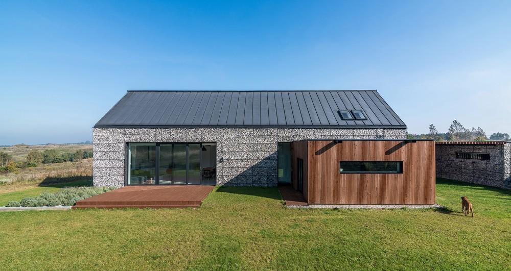 Kuća napravljena od čeličnih koševa punih kamenja