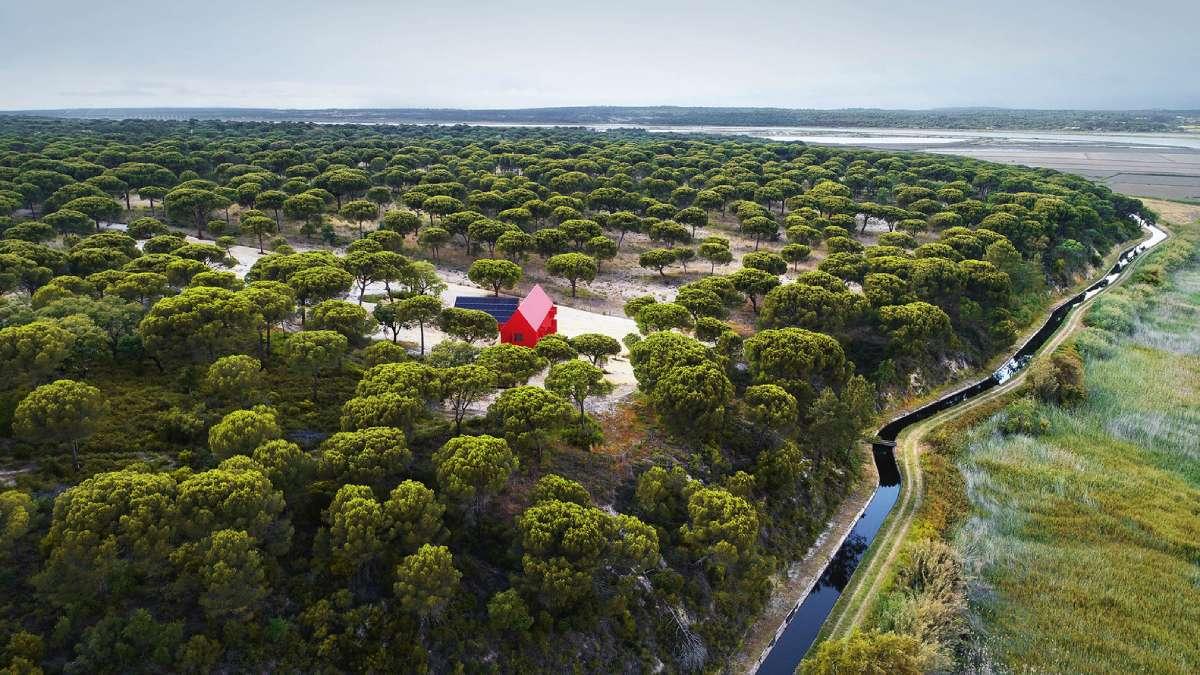 Mala crvena kuća koja je razbila veliko zeleno okruženje